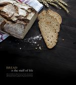 Rustic crusty bread loaf and slices with some wheat ears on dark wood background is fading to black sample text Bread is the staff of live. Concept image for a bakery equally suitable for charities for famine relief. poster