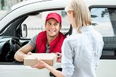 Colorful picture of courier delivers package for woman. Courier is sitting in the car and smiling. Woman accepts the parcel. poster
