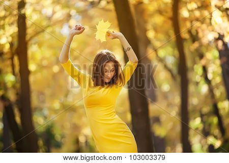 Young woman in the yellow dress with autumn leaves in hand and fall yellow maple garden background