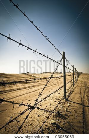 Barbed wire fence in perspective. Protective fence in the deserted area.