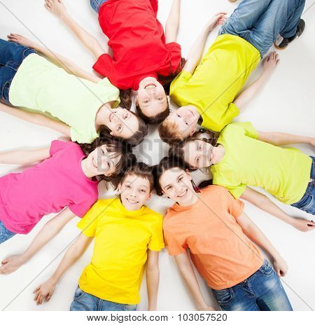 Happy group children isolated at white background. Smiling teen lying in a circle. Frendship boys and girls