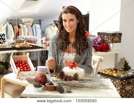 Creative young woman making christmas ornaments centrepiece, smiling, looking at camera.