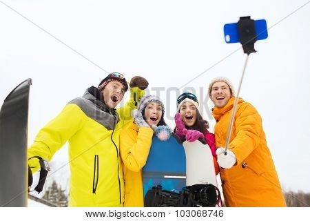 winter sport, leisure, friendship, technology and people concept - happy friends with snowboards and taking picture by smartphone on selfie stick