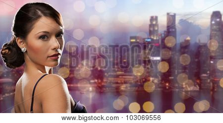 people, holidays, jewelry and luxury concept - woman face with diamond earring over night singapore city and lights background