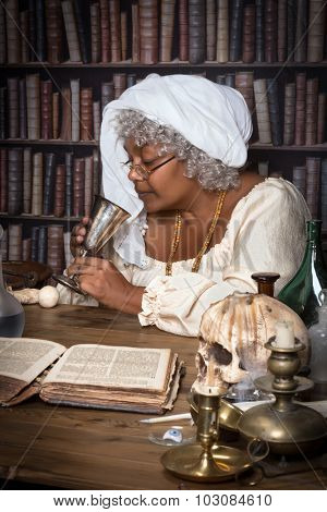 Dark alchemist tasting a brew from her laboratory