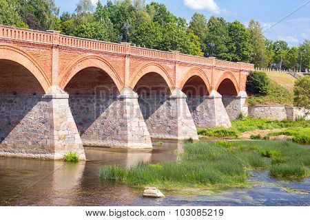 Old brick bridge over river Venta at Kuldiga, Latvia poster