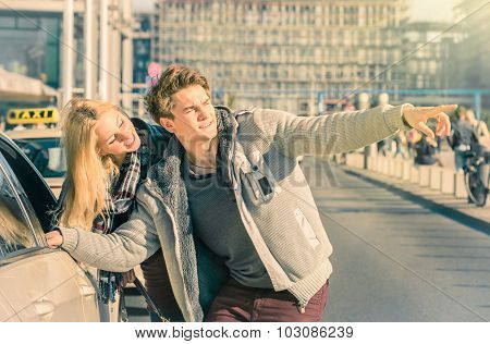 Young Couple Of Lovers Dealing With A Taxi Cab In The City Center - Handsome Man And Beautiful Woman