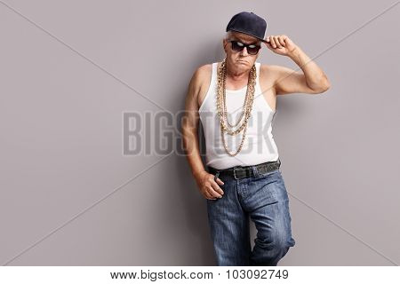 Senior gangster wearing hip-hop clothes and accessories and leaning against a gray wall