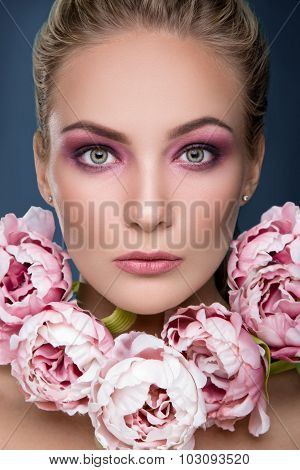 Close up portrait of young blonde woman with sensual makeup and peonies on her neck on blue background. Fashion photo.