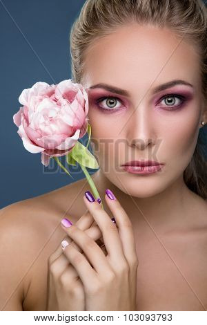 Portrait of a gorgeous blonde woman with delicate makeup holding peony in her hand close up. Fashion photo