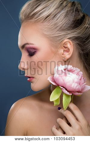 Close-up portrait of beautiful woman with fresh face holding peony flower in her hand on blue background. Fashion photo.