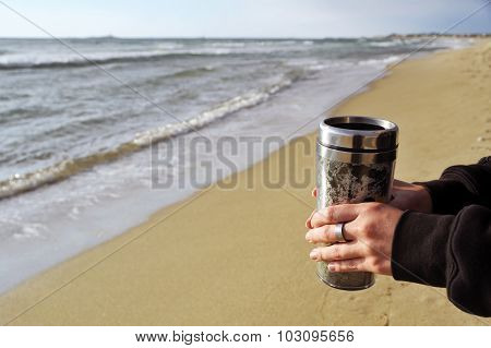 Woman's hands with thermos cup near sea