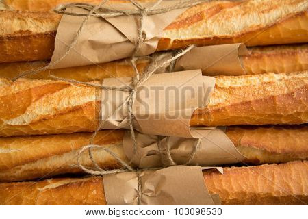 Loafs of French baguette bread tied together with paper and string poster