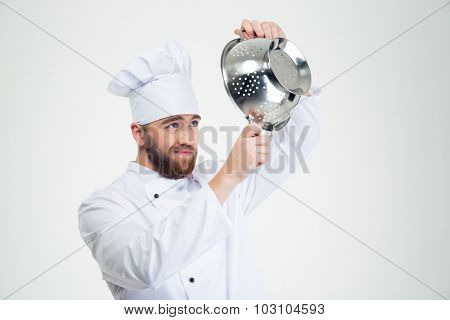 Portrait of a male chef cook holding colander isolated on a white background