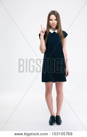 Portrait of a happy young woman pointing finger up at copyspace isolated on a white background. Looking at camera
