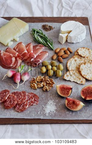 Selection of cured meat charcuterie salami, coppa, with brie camembert gruyere cheese served with olives nuts crackers and fruit