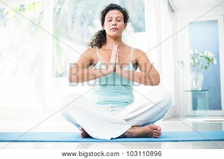 Full length of pregnant woman sitting on exercise mat with hands joined at home