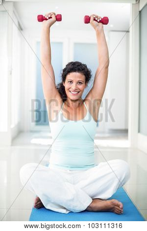 Full length of pregnant woman lifting dumbbells while sitting on exercise mat in fitness studio