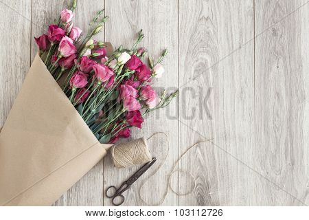 Pink eustoma flowers wrapped in craft paper, twine and vintage scissors on natural wooden floor, selective focus, shabby chic style, space for custom text. poster