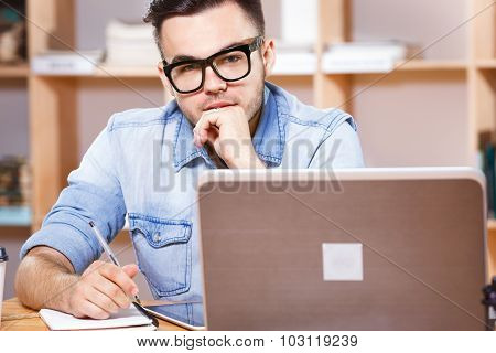 Young brunette man wearing in casual blue shirt and glasses sitting at the table with laptop and looking at camera on the bookshelves background waist up