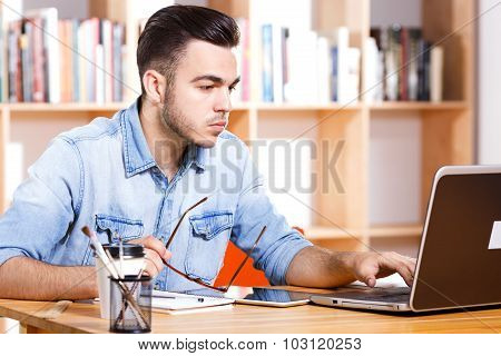 Handsome young businessman wearing in blue casual shirt working on his laptop with cup of coffee on the bookshelves background in office waist up