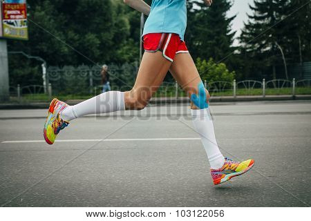 girl athlete running a marathon knees in blue kinesiology taping poster