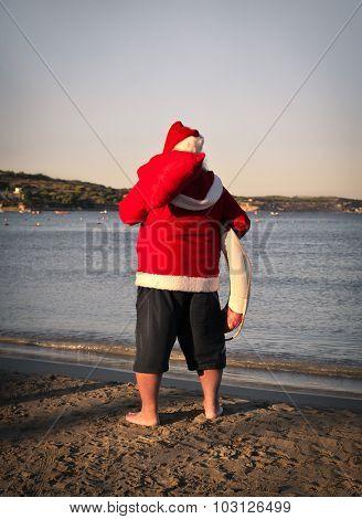 Santa Claus holding a lifebelt at the beach