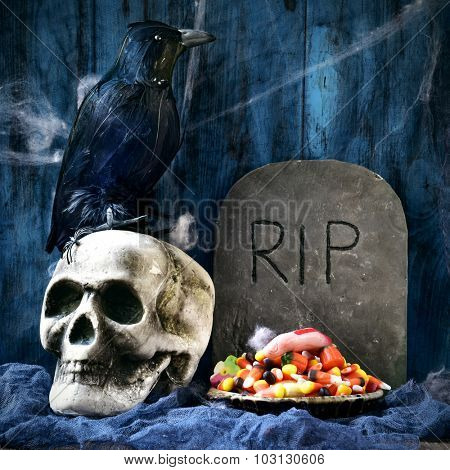 a plate with Halloween candies and an amputated finger in a dismal scene with a crow, a skull and a gravestone with the text RIP carved in