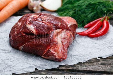 Raw Ox Cheek On Crumpled Paper,  Decorated With Greens And Vegetables. On Old  Wooden Table