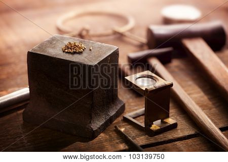 Gold nuggets on a old anvil, with tools in background. intentionally shot in nostalgic tone. Shallow depth of field. poster