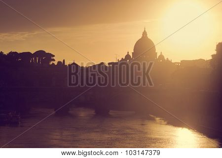 St. Peter's Basilica in Vatican City and Ponte Sant'Angelo bridge over Tiber river in Rome, Italy at sunset. Deem light