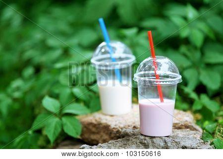 Plastic cups of milkshake on green background, outdoors
