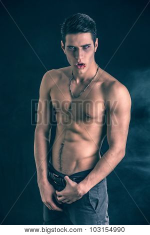 Portrait of a Young Vampire Man Shirtless, Showing his Torso, Chest and Abs, Looking at the Camera, on Dark Background. poster