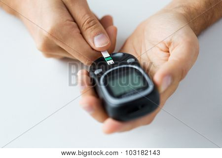 medicine, diabetes, glycemia, health care and people concept - close up of man checking blood sugar level by glucometer and test stripe at home poster
