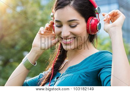 Closeup shot of young woman listening to music in a park. Portrait of happy smiling girl feeling free with music. Close up of latin girl listening to music with headphone and dancing in a city center. poster