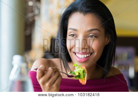 Closeup shot of young woman eating fresh salad at restaurant. Healthy african girl eating salad and looking away. Smiling young woman holding a forkful of salad. Health and diet concept.