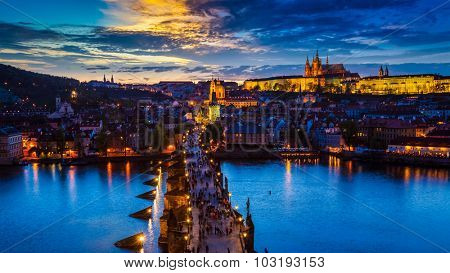 Panorama of illuminated Prague castle and Charles Bridge with tourist crowd over Vltava river in Prague, Czech Republic. Prague, Czech Republic in the evening