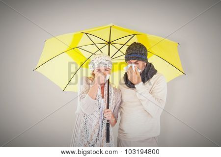 Couple sneezing in tissue while standing under umbrella against grey background with vignette