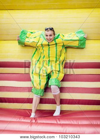 Young Woman In Plastic Dress In A Bouncy Castle Imitates A Fly On Velcro Wall