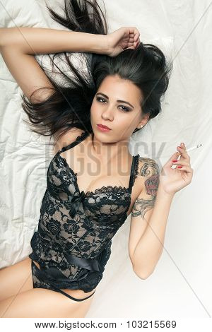 Attractive Brunette Girl In Bed With Cigarette