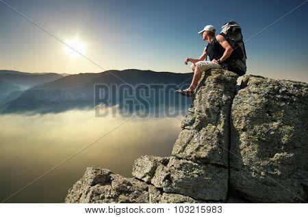 Man tourist on peak of mountain. Travel mountain scene.
