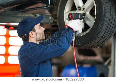 Mechanic changing car wheel in auto repair shop