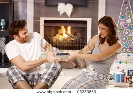 Young couple pulling about christmas present, having fun.