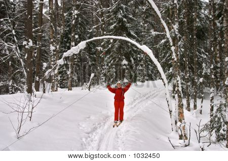 Winter Forest. Woman Skier Smiling With Hands Up