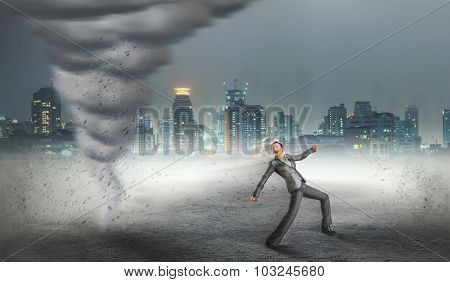 Businesswoman running from the tornado