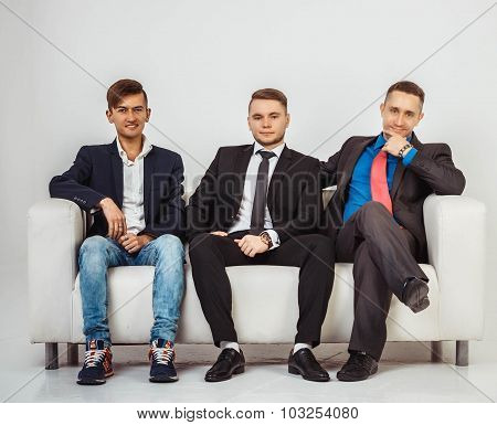 Team Of Three Businessmens Sitting On Couch, Isolated On White Background