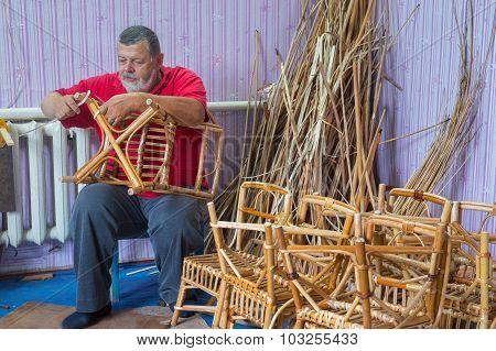 Senior master of wicker-work making a stool poster