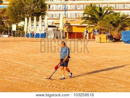 Man with metal detector on the beach of Tossa de Mar.