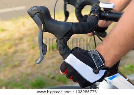 Hands in gloves on bicycle's handlebars