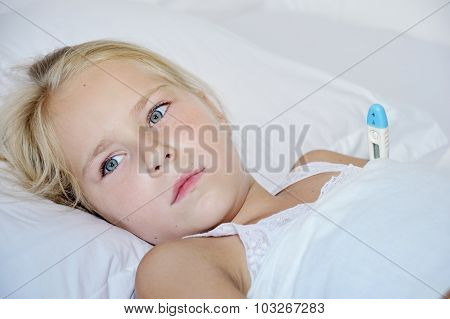 Little Girl With A Thermometer Sick In Bed